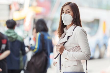 Photo for Asian woman are going to work.she wears N95 mask.prevent PM2.5 dust and smog. - Royalty Free Image