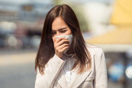 Photo pour Asian woman are going to work.she wears N95 mask.prevent PM2.5 dust and smog.she is coughing - image libre de droit