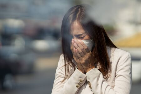 Photo for Asian woman are going to work.she wears N95 mask.prevent PM2.5 dust and smog.she is coughing - Royalty Free Image