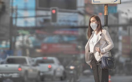 Foto de Asian woman are going to work.she wears N95 mask.Prevent PM2.5 dust and smog - Imagen libre de derechos