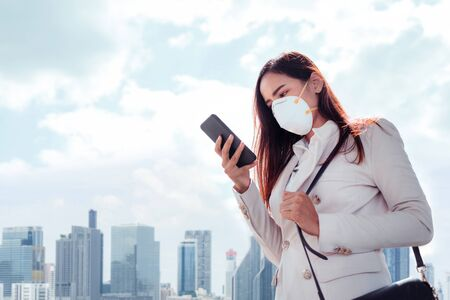 Photo pour Asian woman are going to work.she wears N95 mask.prevent PM2.5 dust and smog - image libre de droit