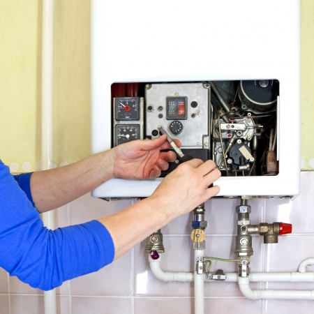 Photo for repairman fixing a gas heating with screwdriver - Royalty Free Image