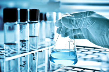 Foto de Flask in scientist hand and laboratory glassware background - Imagen libre de derechos