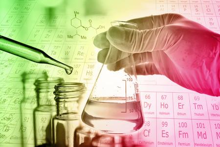Foto de Flask in scientist hand with test tube in rack - Imagen libre de derechos