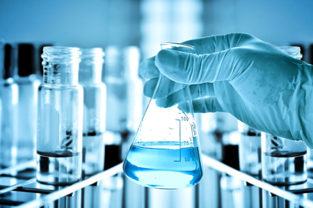 Foto de Flask in scientist hand with laboratory background - Imagen libre de derechos