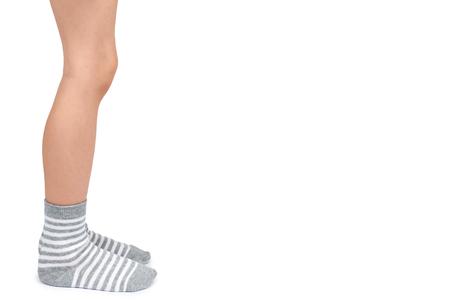 Foto de Kid legs in striped socks isolated on white background, copy space template. - Imagen libre de derechos
