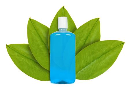 Foto de Blue bottle with mouthwash on the background of green leaves. Isolated on white. concept of natural origin - Imagen libre de derechos