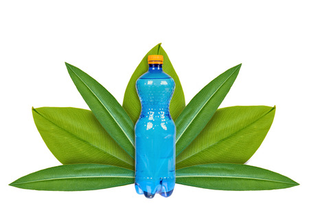 Foto de Plastic bottle of drinking water on the background of green leaves. Isolated on white. concept of natural origin - Imagen libre de derechos
