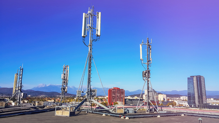 Foto de Cellular network antenna radiating and broadcasting strong power signal waves over the city on a building roof with telecommunication mast - Imagen libre de derechos