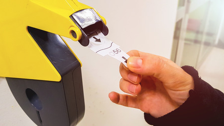 Photo for Customer pulls with hand a numbered ticket out of yellow number dispenser machine, to wait in service line and to be served when his number is displayed - Royalty Free Image