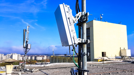 Foto de 5G mobile telecommunication smart cellular radio network antennas on a mast on the roof broadcasting signal waves over the city on a clear sunny day with blue sky and clouds close up - Imagen libre de derechos