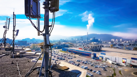 Foto de Mobile telecommunication cellular radio network antennas on a mast on the roof broadcasting signal waves over the city on a clear sunny day with blue sky and clouds - Imagen libre de derechos