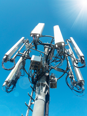 Foto de Mobile telephone network base station telecommunication tower with smart cellular antennas radiating and broadcasting strong digital signal waves from view from the top - Imagen libre de derechos