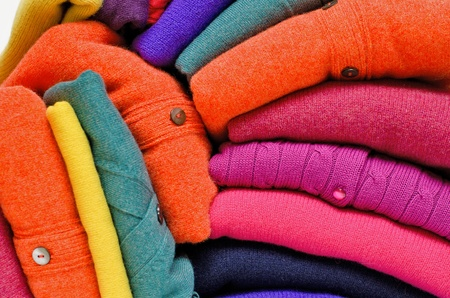 Stack of women\'s sweaters and cardigans in bright vivid colours against white.