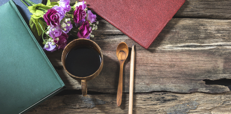 Photo for Top view black coffee mug with notebook and flower. - Royalty Free Image