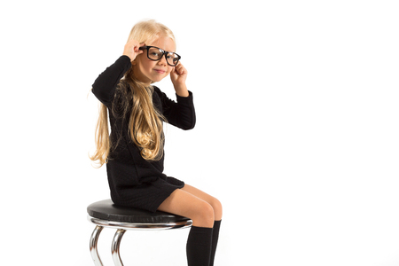 Photo for Isolated on white, pretty caucasian blonde little girl in black dress, glasses, black socks and white shoes sitting, hands on the head - Royalty Free Image