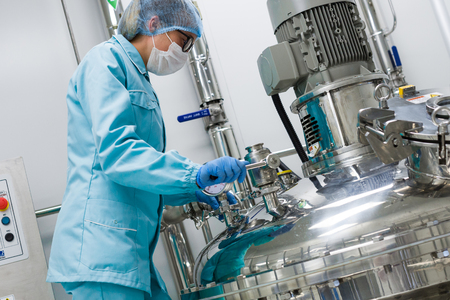 Foto per scientist woman in blue suit is checking pressure on tank - Immagine Royalty Free
