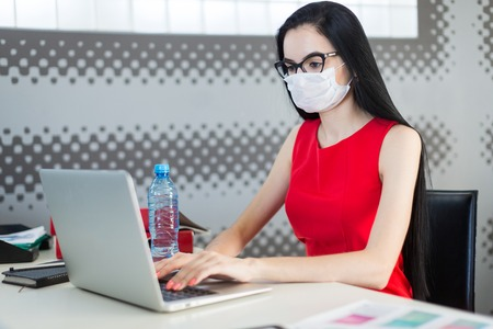 Photo for Office on background, pretty, young brunette caucasian businesslady in red dress, respirator and glasses sit at the table and work with laptop, water bottle on the table - Royalty Free Image