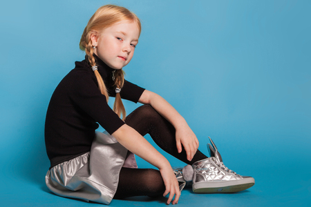 Photo pour isolated on blue, red-haired girl with braids in black sweater with zipper, black tights, silver skirt and sneakers, sitting and looking arrogantly into the camera. copyspace. - image libre de droit