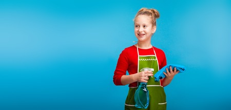 Photo for a pretty little girl holding cleaning products doing housework - Royalty Free Image