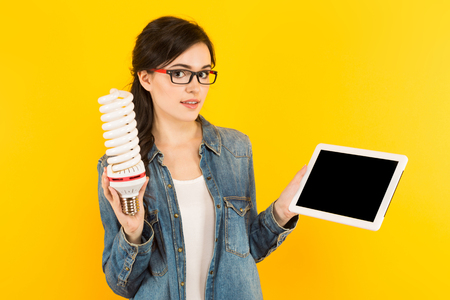 Photo pour Portrait of attractive happy woman in denim shirt and eyeglasses isolated on yellow background holding light bulb working on laptop new ideas with innovation and creativity concept. - image libre de droit