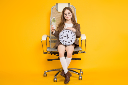 Photo pour Long-haired little girl in eyeglasses sits in chair wearing brown jacket, shorts and white knee-socks with watches and fan of euro bills isolated on orange background with copyspace time is money. - image libre de droit