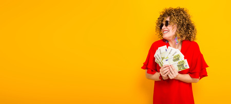 Foto de White happy woman with afrro hairstyle in red dress and sunglasses holding fan of euro bills isolated on orange background with copyspace winning in lottery money withdraw concept horizontal picture. - Imagen libre de derechos