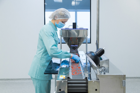 Foto für Pharmaceutical technician in sterile environment working on production of pills at pharmacy factory - Lizenzfreies Bild