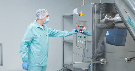Foto de Pharmaceutical technician in sterile environment at pharmacy industry - Imagen libre de derechos