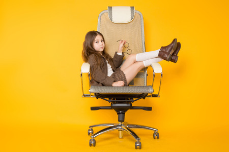 Foto de Portrait of long-haired little girl in eyeglasses sits in armchair wearing brown jacket, shorts and white knee-socks isolated on orange background with copyspace kids fashion concept. - Imagen libre de derechos