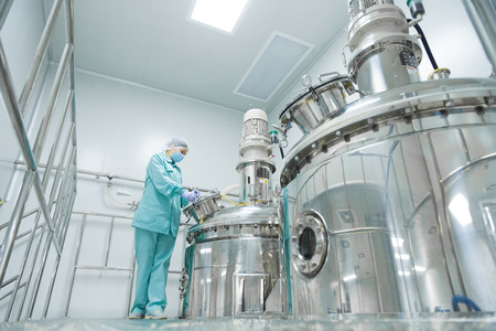 Foto de Pharmaceutical technician in sterile environment at pharmacy industry - Imagen libre de derechos