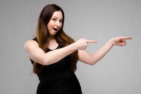 Foto de Emotional plus size model standing in studio pointing fingers outstretched hands to the right showing on blank area - Imagen libre de derechos