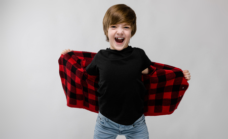 Photo pour Portrait of cheerful little boy holding his checkered jacket spread and screaming at camera isolated on grey background with copyspace childrens fashion concept. - image libre de droit