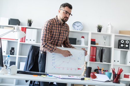 Photo for A bearded man in a plaid shirt, glasses and dark trousers works in a bright office. photo with depth of field. - Royalty Free Image