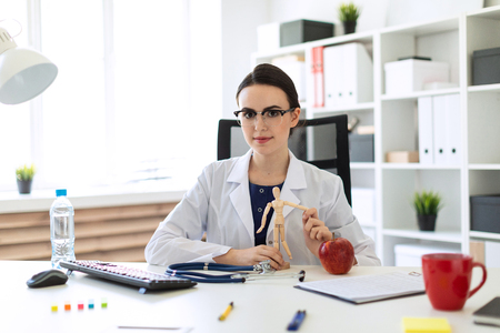 Photo for A charming young girl with glasses, a blue blouse and a white robe is sitting in the office. A stethoscope lies on the table in front of the girl. - Royalty Free Image