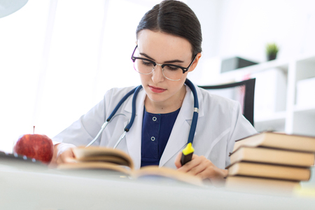 Foto de A charming young girl with glasses, a blue blouse and a white robe is sitting in the office. The girl has a stethoscope on her neck. photo with depth of field. - Imagen libre de derechos