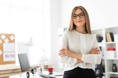 Foto de Beautiful young blonde girl in white blouse and black skirt is working in the office. photo with depth of field - Imagen libre de derechos