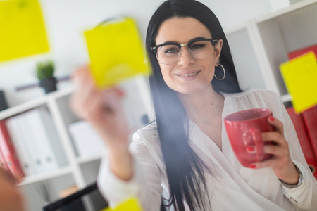 Foto de A young girl with glasses, wearing a white blouse and black trousers, works in the office. The girl has long straight black hair. photo with depth of field - Imagen libre de derechos
