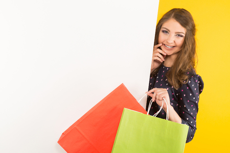 Photo pour Portrait of attractive happy brunette woman in blouse isolated on yellow background holding colourful shopping paper bags near white empty blank board your text here advertising concept. - image libre de droit