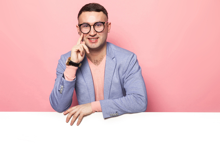 Photo pour Portrait of handsome thoughtful businessman in blue jacket and eyeglasses isolated on pink background leaning on emty blank board and propping up his cheek your text here concept. - image libre de droit