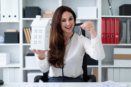 Foto de Beautiful girl working in a bright office. The girl is dressed in a business suit. She has long dark hair and beautiful makeup. photo with depth of field. The photo depth of focus, a dedicated focus on the hands. - Imagen libre de derechos
