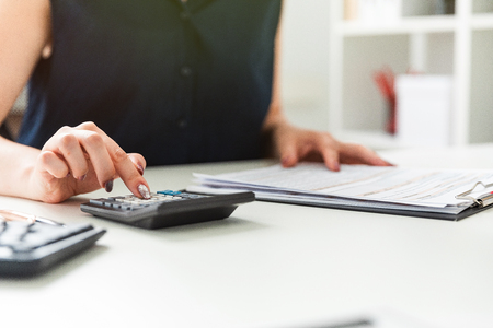 Photo pour Graceful womens hands leaf through the form and click on the calculator. Charming young girl working in a bright office. photo with depth of field - image libre de droit