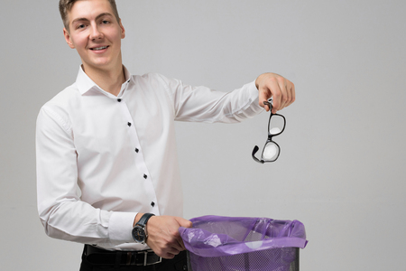 Photo for business man in white shirt holding glasses for vision over trash can and smiling. young man gets rid of his glasses. place for label - Royalty Free Image