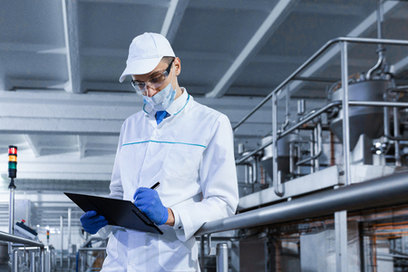 Foto de technologist in the cap, mask and white coat stands in the production shop and makes notes with a pen in the sheet. The inspector removes the indicators at the dairy plant. Engineer keeps statistics on production - Imagen libre de derechos