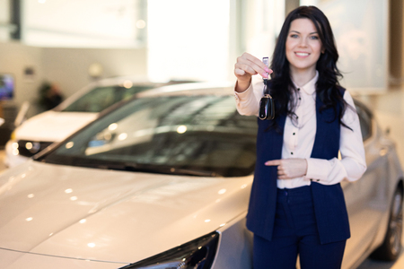 Photo for Portrait of smilling happy woman handing a key of her new vehicle - Royalty Free Image