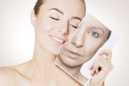 Photo pour closeup portrait of young woman face holding portrait with old wrinkled face - image libre de droit