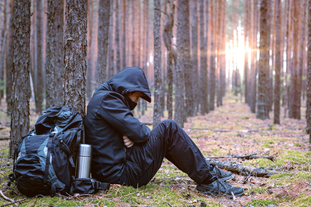 Photo for Frozen tired traveler man at halt. Tourist is resting in the forest. Copy space - Royalty Free Image