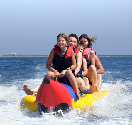 Photo pour happy people having fun on banana boat on the red sea - image libre de droit