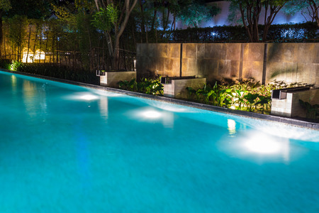 Photo pour Pool lighting in backyard at night for family lifestyle and living area.  Luxury design with good light and clean landscaping. - image libre de droit