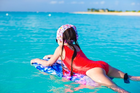 Photo for Little cute girl swimming on a surfboard in the turquoise sea - Royalty Free Image